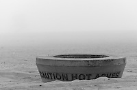 "A fire pit on the sand at Huntington State Beach in Huntington Beach, CA on a foggy New Year's Eve.  The beach was nearly empty for this gorgeous foggy sunset.  It reads ""Caution hot ashes""."