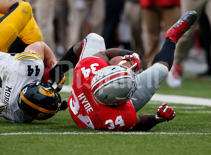 Ohio State Buckeyes running back Carlos Hyde (34) is tackled by Iowa Hawkeyes linebacker James Morris (44) in the fourth quarter of their game at Ohio Stadium in Columbus, Ohio on October 19, 2013. Columbus Dispatch photo by Brooke LaValley)