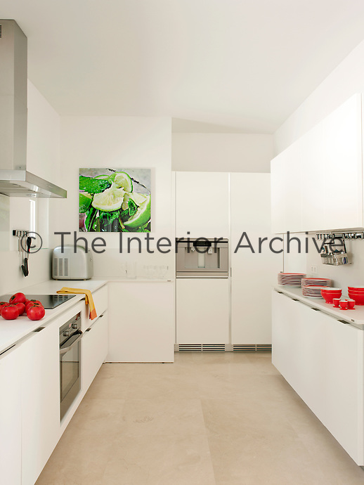 A modern, white kitchen with a sand-blasted stone floor. An artwork on the wall and tableware provide bright accent colours of green and red.