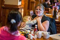 A mother comforts her daughter who is about two or three years old with a breastfeed while sitting at a table in the family restaurant and play area ofn a pub.