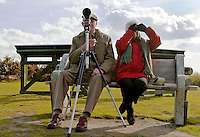 An elderly man and woman use a telescope and binoculars to watch birds at Cliffe Pools nature reserve Kent, UK.  April 16th 2008