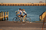 Two young women riding bikes along the water front