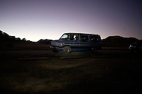 A van stands parked in a campground outside Badlands National Park in South Dakota, USA.