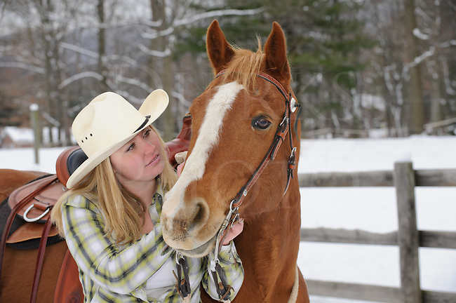 Pretty blonde woman looking at her horse with affection while outdoors in winter, twenty-something young causcasian female in casual western dress with cowboy hat and flannel shirt, Pennsylvania, PA, USA.