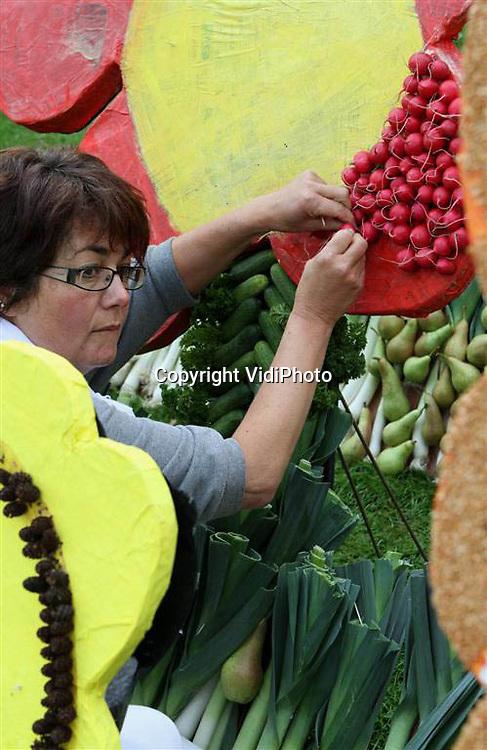 Foto: VidiPhoto..TIEL - Ter voorbereiding op het 50e fruitcorso, dat op 11, 12 en 13 september plaatsvindt, zijn zo'n 25 verenigingen, instellingen, scholen en organisaties donderdag aan de slag gegaan met het leggen van zogenoemde fruitmozaïeken. De afbeeldingen van fruit- en groentensoorten zijn vanaf vrijdag te zien op de stadswallen in Tiel. Het gebruikte fruit en groenten zijn de restanten die overblijven bij het versieren van de fruitwagens.