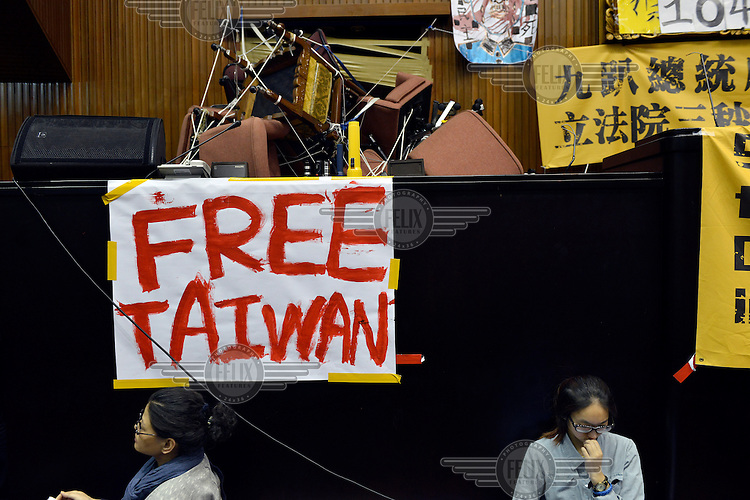 "Students sit below a sign which reads: 'Free Taiwan' next to a barricade which they have erected in front of the door of  the Legislative Yuan (Parliament) Building to keep out police. They have been occupying the building for days to express their opposition to the passing of the Cross-Straight Service and Trade Agreement between Taiwan China.  The students, and many normal Taiwanese, fear the erosion of their hard-won democracy and, eventually, independence, making them, in the words of one student protestor 'no better off than Hong Kong'. Ma ying-jeoh bears the brunt of the protestors ire; known as ""Ma 9%"" after his latest approval rating, he is seen as kowtowing to the demands of China and selling out Taiwan."