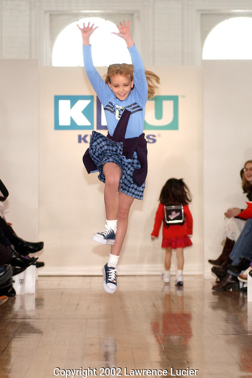 Model Jamie Lynn Spears begins a cartwheel while wearing a blue long sleeve graphic cheerleader tee with a blue plaid skirt and blue zip-front sweater  April 11, 2002, in New York. This item is part of the Fall 2002 Kids R Us fashion collection. .