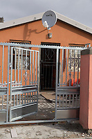 South Africa, Cape Town, Guguletu Township.  Middle-class House with Satellite Dish and Security Gate.