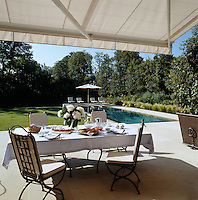Ville d'Avray chairs by Herve Baume surround a table laid for breakfast in the shade of an awning on the terrace