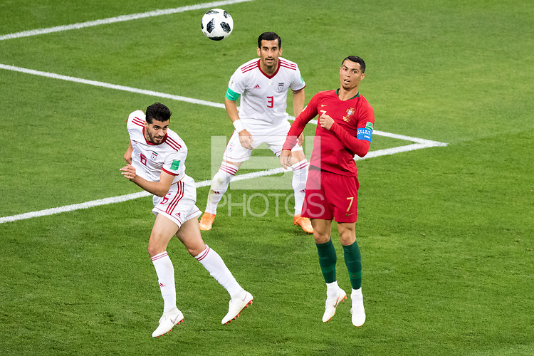 SARANSK, RUSSIA - June 25, 2018: Saeid Ezatolahi of Iran heads a ball past Cristiano Ronaldo of Portugal while Ehsan Hajsafi of Iran looks on in their 2018 FIFA World Cup group stage match at Mordovia Arena.