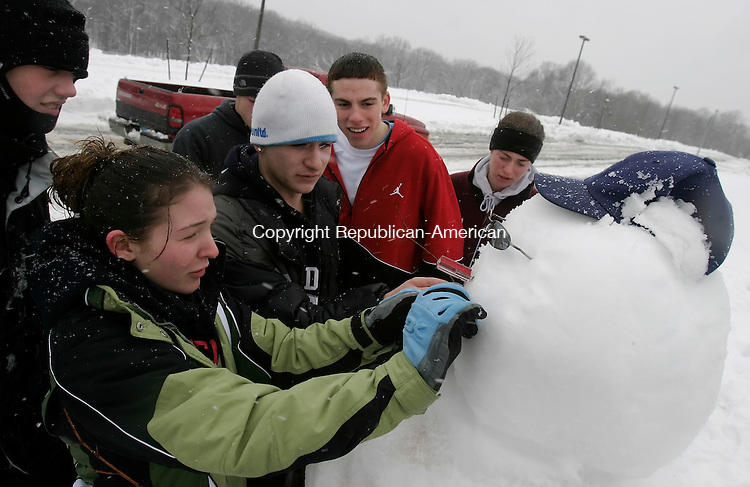 SOUTHBURY, CT 03 January 2005 -010305BZ05-  From left- Ross Therrien, 17; Amanda Major, 17; Will Crick, 17; Steve Halas, 17, in background; Brian McDonald, 17; and Paige Moore, 17; were just a few of a larger group of Pomperaug High students who built a snowman in front of the sign at the school in Southbury Tuesday afternoon.<br /> Jamison C. Bazinet Republican-American