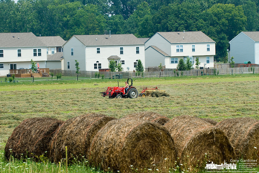 A farmer rakes hay ready for baling on a small farm adjacent to a recently built neighborhood on former farm land near Lewis Center, Ohio.<br />