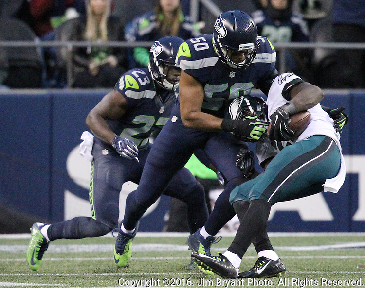 Seattle Seahawks outside linebacker K.J. Wright (50) and safety Steven Terrell (23) wrestle down Philadelphia Eagles Running back Wendell Smallwood (28)<br /> at CenturyLink Field in Seattle, Washington on November 20, 2016.  Seahawks beat the Eagles 26-15.   &copy;2016. Jim Bryant Photo. All Rights Reserved.
