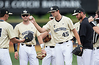 Wake Forest Demon Deacons relief pitcher John McCarren (45) hands the ball off to teammate Carter Bach (18) as he is taken out of the game against the Pitt Panthers at David F. Couch Ballpark on May 20, 2017 in Winston-Salem, North Carolina. The Demon Deacons defeated the Panthers 14-4.  (Brian Westerholt/Four Seam Images)