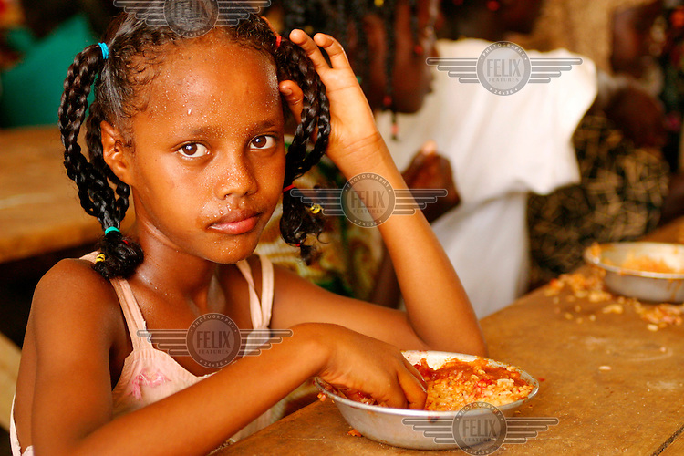 A young girl eating a meal at school.