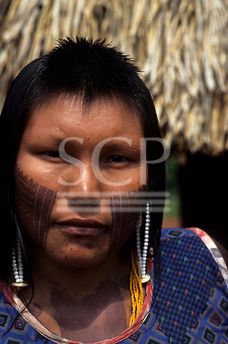 A-Ukre Village, Brazil. Kayapo woman with intricate black genipapo face painting and bead ear rings and necklaces.