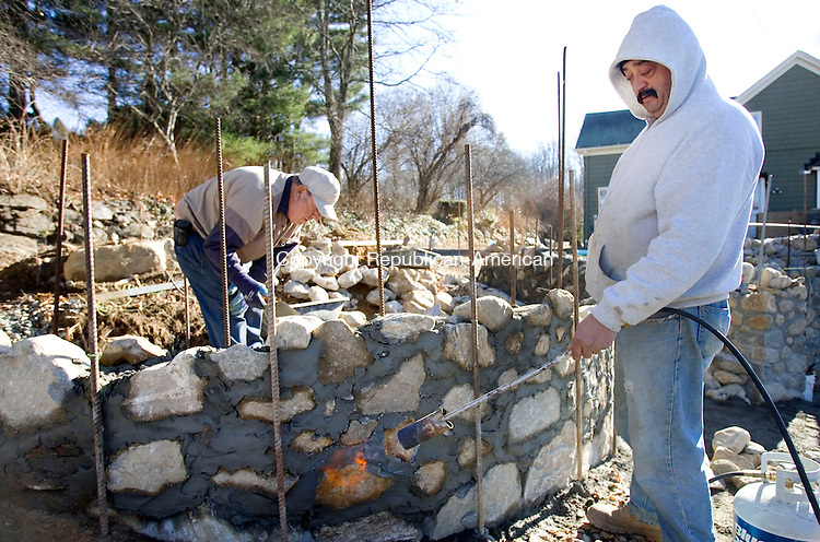 WATERBURY, CT. 30 November 2010-112910SV03--From left, Leo Orsini, of A &amp; A Services, works on a stone wall as Joe Addona heats the cement with a flame on Whittemore Road in Middlebury Monday. Work on the wall continues all week and the flame is needed to cure the cement in the cold weather.<br /> Steven Valenti Republican-American