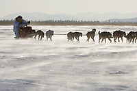 Paul Gebhardt sits behind his sled as he runs on the Yukon river between Eagle Island & Kaltag in 35-40 mph wind