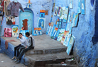 Boys selling paintings on a street corner painted blue, in the medina or old town of Chefchaouen in the Rif mountains of North West Morocco. Chefchaouen was founded in 1471 by Moulay Ali Ben Moussa Ben Rashid El Alami to house the muslims expelled from Andalusia. It is famous for its blue painted houses, originated by the Jewish community, and is listed by UNESCO under the Intangible Cultural Heritage of Humanity. Picture by Manuel Cohen