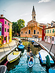 Paddle boarder travel a canal toward the church and leaning tower, the colorful village of Burano, Italy.