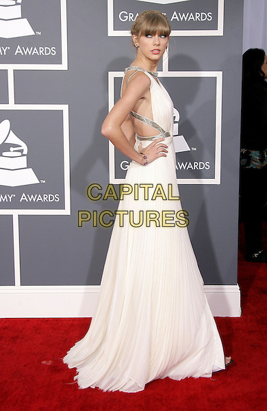 Taylor Swift.The 55th Annual GRAMMY Awards held at STAPLES Center, Los Angeles, California, USA..February 10th, 2013.grammys full length white silver gold side straps dress hands on hips fringe bangs hair cut out away pleats pleated  .CAP/ADM.©AdMedia/Capital Pictures.
