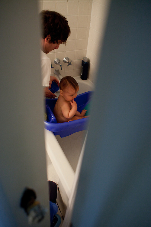 My husband, gives our younger son, almost one, a bath.