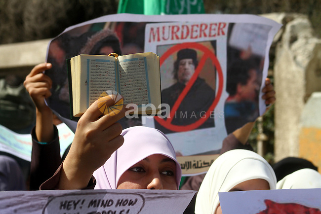 "Palestinian students hold up the Koran and placards during a protest against Libyan leader Moamer Kadhafi, in Gaza City on February 22, 2011. Gaza's Hamas rulers heaped condemnation on ""the massacres"" of anti-government protestors in Libya committed by regime of embattled veteran leader Moamer Kadhafi. Photo by Ashraf Amra"
