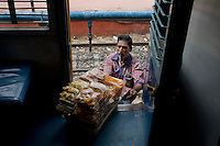 A food vendor hops onto the train to sell Muruku, an array of South Indian snacks, as it stops for 20 minutes at Erode Junction stn., Tamil Nadu on 9th July 2009.. .6318 / Himsagar Express, India's longest single train journey, spanning 3720 kms, going from the mountains (Hima) to the seas (Sagar), from Jammu and Kashmir state of the Indian Himalayas to Kanyakumari, which is the southern most tip of India...Photo by Suzanne Lee