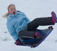 A young girl goes airborne at the bottom of a snow-covered slope on the facing edge of a reservoir dam in Columbus, Ohio, Thursday, December 23, 2004. A winter storm covered central Ohio with as much as a foot of snow and an inch of ice forcing school and business closings. Photo by Gary Gardiner, The Eyepush Network