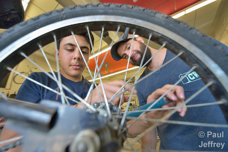 Mohammad Khilo (left), a refugee from Syria, works on a bike at The Common Wheel in Lancaster, Pennsylvania, supervised by Chris Caldwell, the community bike center's executive director. The Common Wheel collaborates with Church World Service to help resettled refugees own, maintain, and use bicycles.<br /> <br /> Photo by Paul Jeffrey for Church World Service.