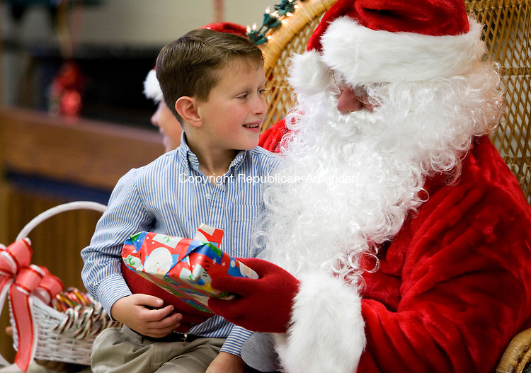 WATERBURY, CT - 06 DECEMBER 2009 -120609JT04--<br /> Connor Fahy, 6, of Woodbury, visits with Santa Claus during Sunday's annual Catholic Charities Holiday Adoption Party at Holy Cross High School in Waterbury. Behind Fahy, partially obscured, is Santa's helper Jonathan Ernt, 12, of Southbury. Families from throughout the Hartford Archdiocese attended, representing both domestic and international programs of Catholic Charities. <br /> Josalee Thrift Republican-American
