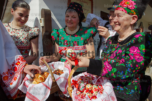 Local women offer cookies and painted eggs to guests as part of the traditional easter celebrations, during a media presentation in Mezokovesd, Hungary on April 5, 2012. ATTILA VOLGYI