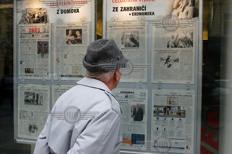 In the window of the DNES newspaper office, a man reads that day's paper.