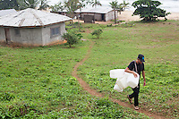 Jon Rose carries containers to be used for water filtration systems in Robertsport, Liberia. The W4W systems are very easy to make, needing only a container (bucket, tub, jerrycan, etc) and the water filter that Waves 4 Water distributes.