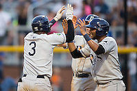 Adrian Rondon (3) of the Princeton Rays is greeted at home plate by teammates Rafelin Lorenzo (8) and Bobby Melley (38) after hitting a 3-run home run against the Burlington Royals at Burlington Athletic Stadium on June 24, 2016 in Burlington, North Carolina.  The Rays defeated the Royals 16-2.  (Brian Westerholt/Four Seam Images)
