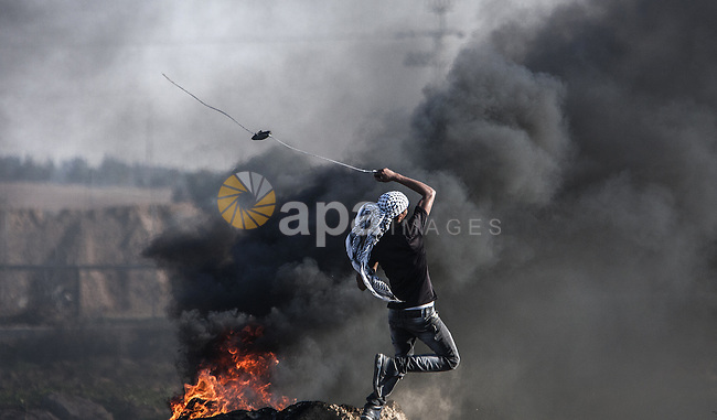 A Palestinian protester uses a sling shot to throw stones towards Israeli troops during clashes near the border between Israel and central Gaza strip, November 13, 2015. The current wave of violence erupted in mid-September, fueled by rumors that Israel was trying to increase Jewish presence in Jerusalem then quickly spread across Israel, the West Bank and the Gaza Strip. Photo by Mohammed Dahman
