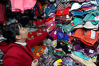 Liu Yanxiu peruses through a wall of colorful bras as she shops for new clothing to wear in the days following her wedding at a market in Guangdong province, China on January 26, 2007.