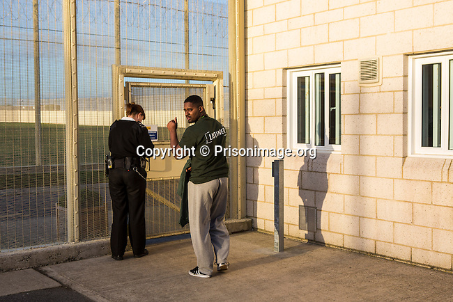 A prisoner is escorted through a locked gate by an officer back to his wing. HMP/YOI Portland, Dorset. A resettlement prison with a capacity for 530 prisoners. © prisonimage.org.  Any image use must be agreed first. All images must be credited.