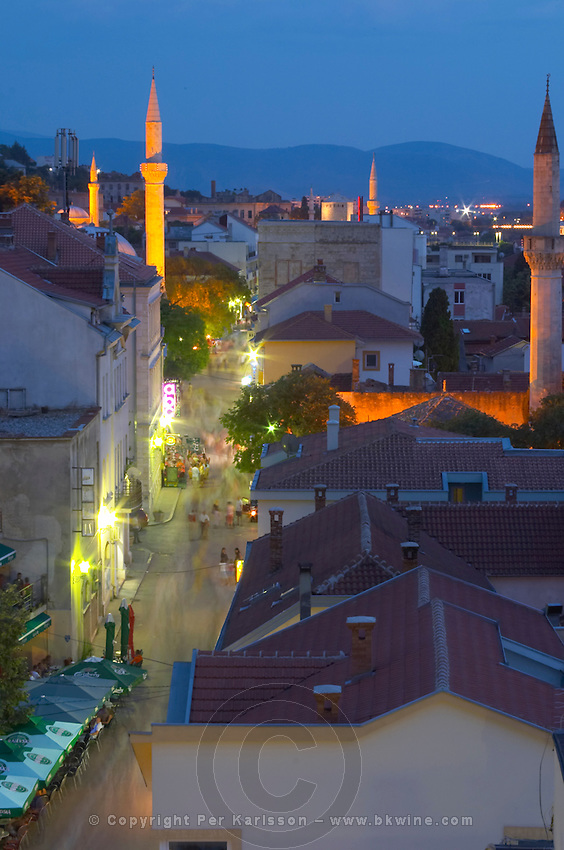 View over the city at sunset. Along The sopping, pedestrian and cafe street Brace Fejica. Mosque minarets. Historic town of Mostar. Federation Bosne i Hercegovine. Bosnia Herzegovina, Europe.