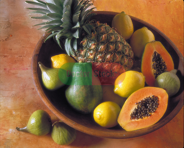 bowl with pineapple, papayas, lemons and figs