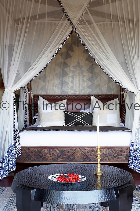 A bedroom in furnished in tribal patterns and a four poster bed at the Singita Pamushana Lodge, Malilongwe Trust, Zimbabwe