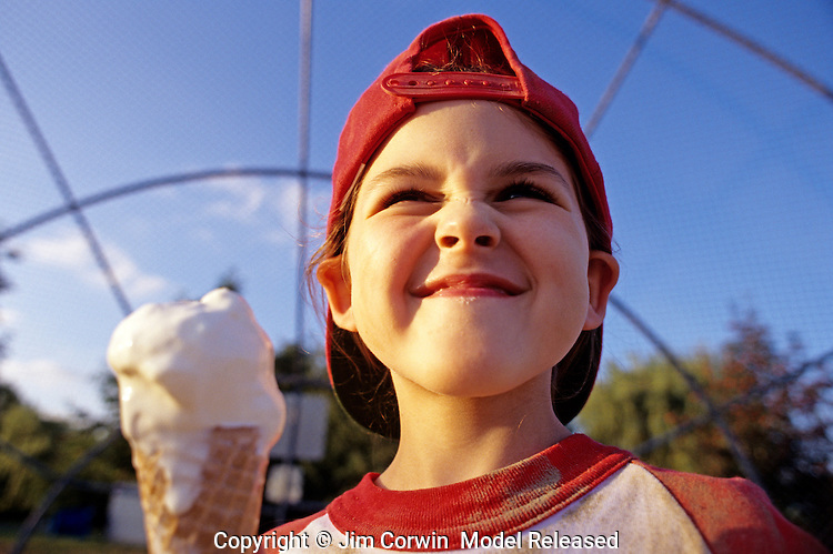 Young girl (7 years old), Little League Baseball player, eating ice cream after game, sunset light, portrait, Woodinville, Washington USA   MR