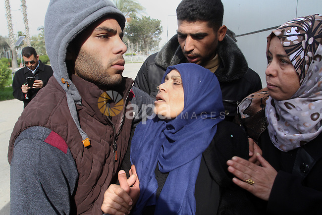 The mother of Palestinian Ishaq Hassan, 28, who was killed by Egyptian soldiers after swimming into Egyptian waters mourns during the arrival of an ambulance carry his body from the Egyptian side of Rafah border crossing at the southern Gaza Strip, on Dec. 31, 2015. Egyptian authorities opened the tightly controlled Rafah Crossing to let the corpse of the Palestinian man killed by Egyptian soldiers into the Gaza Strip. Hassan's family have said he was attempting to reach Egyptian hospitals in order to receive treatment for a disease that could not be treated in Gaza. Photo by Abed Rahim Khatib