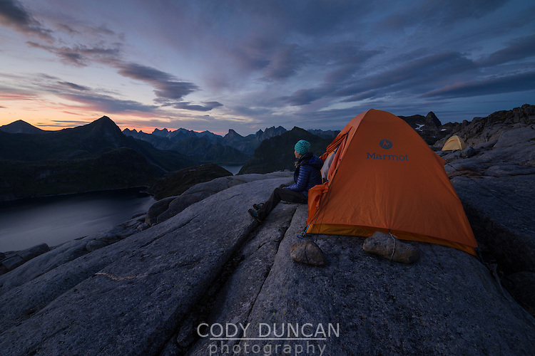 Female hiker sits in from of tent under last twilight light in late summer near summit of Moldtind, Moskenesøy, Lofoten Islands, Norway
