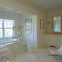 The large bathroom has a relaxing and tranquil atmosphere thanks to the cream and white colour scheme and cool limestone flooring