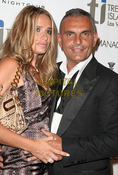 IRA & CHRISTIAN AUDIGIER .Designer Christian Audigier celebrates the Grand Opening of Christian Audigier the Night Club with Guest DJ Nick Cannon inside the Treasure Island (TI) Hotel and Casino, Las Vegas, Nevada, USA,  2 July 2008. .half length wife husband married couple tanned gold snakeskin print bag black grey dress gray.CAP/ADM/MJT.©MJT/Admedia/Capital Pictures