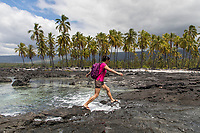 A visitor jumps over the incoming tide at the shoreline, Pu'uhonua o Honaunau in Kona, Hawai'i Island.