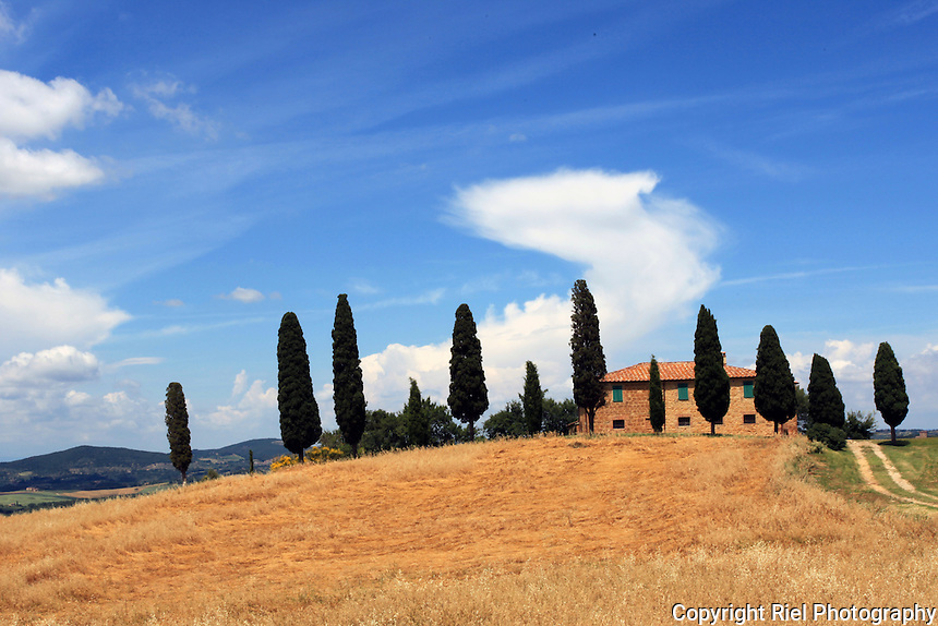 A classic Tuscany farmhouse with cypress trees and a harvested wheat field.
