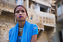 Rajasthani girl in blue dress and traditional Rajasthani jewelry in front of historical building in Jaisalmer Fort, Jaisalmer, Rajasthan, India --- Model Released