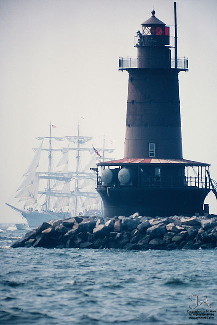 West Bank Light with three masted sailing ship during Operation Sail, 1976  The man on the lighthouse is using binoculars.